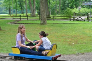 Katie and a new friend play on old fashioned hand-carts at Idlewild Amusement Park
